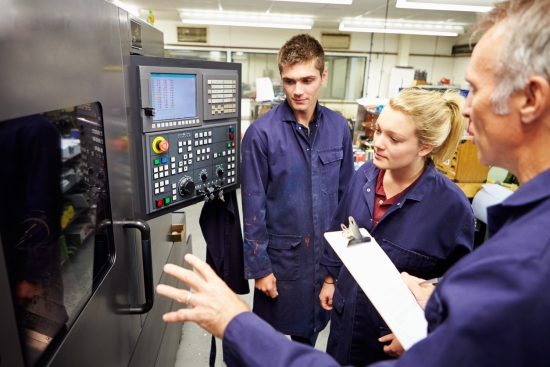 Trained Engineer Teaching Apprentices To Use Computerized Lathe At Work